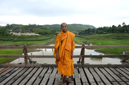 Buddhist monk standing on the bridge, the longest in Thailand. Editorial