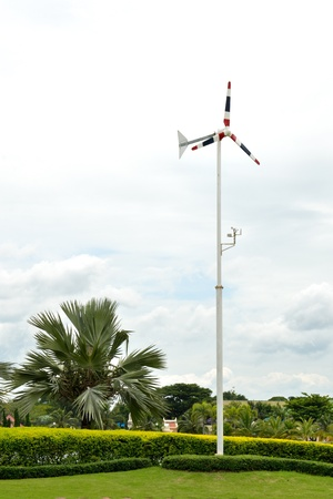 Red, blue and white windmill surrounded by trees and green grass, beautiful weather and cloudy skies. photo