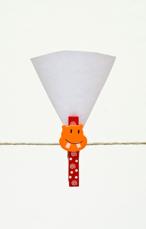 a colorful Clothes pin holding sheets of paper isolated over a white background  photo