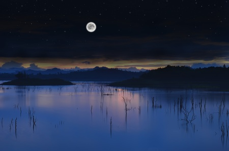 Landscape Lake with full moon and a starry sky.