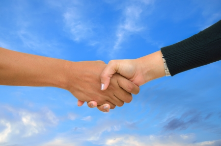 businessmen handshake: hand shake on a background of the blue sky