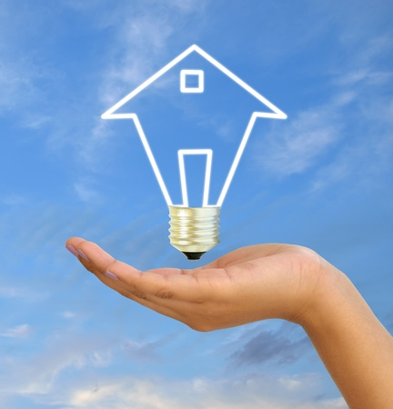 light bulb model of a house in women hand on sky