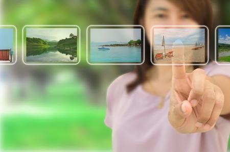 agencia de viajes: Mujer joven con �xito la planificaci�n de su vacaciones en la elecci�n de opciones desde la pantalla de toque digital,