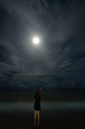 Woman Standing at the beach in the night full moon photo