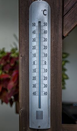 Thermometer calibrated in degrees celsius on the wooden wall, concept of world hot and weather.