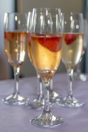 Beautifully decorated welcome drink - a glass of Prosecco or champagne with raspberry inside, served as a welcome drink on a event, party, wedding, reception or banquet.