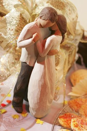 A wooden figurine featuring a dancing couple surrounded by wedding paraphernalia Stock Photo