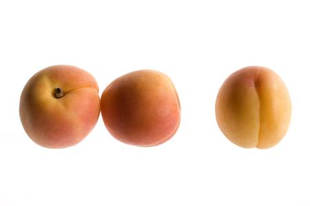 Count em; three peaches on a glowing white backdrop.