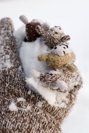 Cute monkey gloves holding a fistful of snow Reklamní fotografie