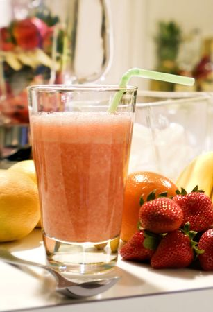 A freshly prepared fruit smoothie in the kitchen.  photo