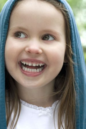 Four year old grinning from ear to ear, looking mischievously to the side.  Stock Photo