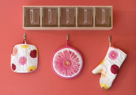 A fun glass organizer with colorful flower oven mitt and potholder.  photo