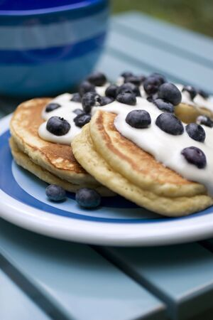 Pancakes covered in whipped cream and blueberries