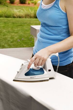 Young woman ironing sheets outdoors