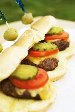 Cute sliders with olive garnish at an outdoor dinner party. Stock Photo