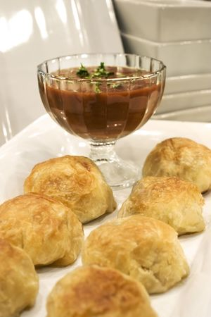 Seven beef and lobster wellingtons served with gravy on a porcelain plate.