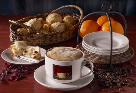An assortment of breakfast foods, including muffins and coffee.