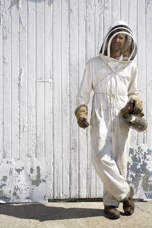 Relaxed beekeeper in front of barn