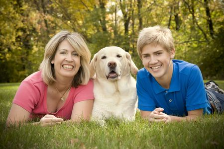 A mom and teenage son posing with their yellow lab Stock Photo
