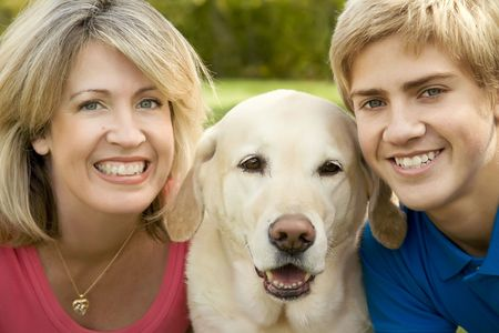 A mom and teenage son with their yellow labrador photo
