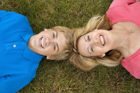 A mom and teenage son lying head to head in the grass photo