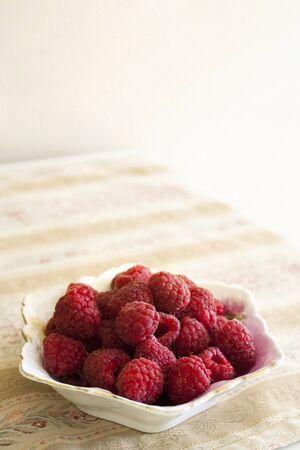 flowered: Bowl of Raspberries on flowered Fabric