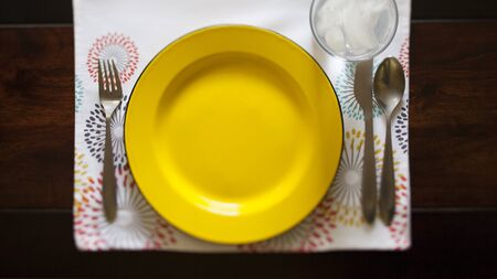 full place setting with yellow plate on patterned place mat