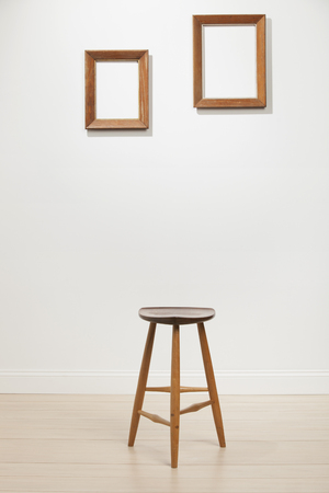 frame wall: empty frames and chair on a white wall, interior Stock Photo