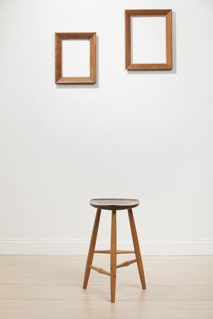 silla: empty frames and chair on a white wall, interior Foto de archivo