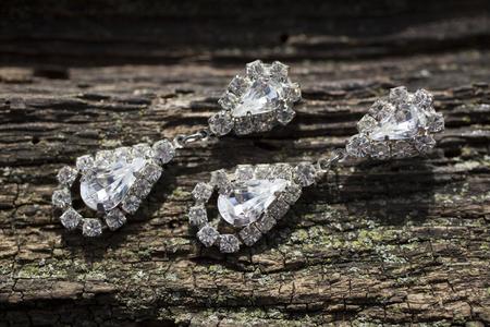 diamond earrings: pair of diamond earrings on brown wooden texture