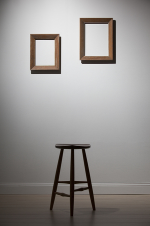 after hours: empty frames and chair on a white wall, interior Stock Photo