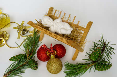 Christmas decoration, baby Jesus is sleeping on the hay, pine cone, golden bell, green ribbons, golden gift, on a light background