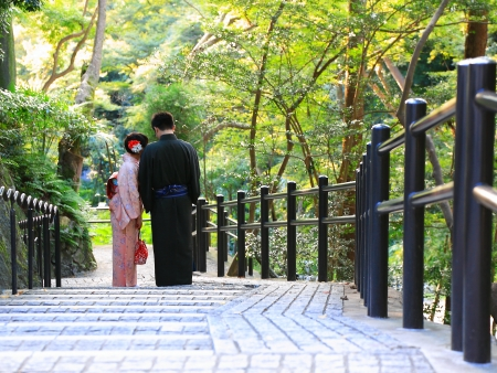 Japanese couple in traditional dress stand in the temple Banco de Imagens