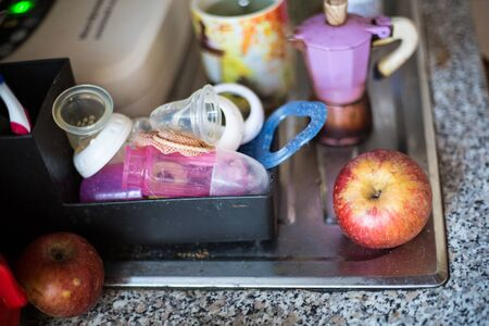 Kitchen still-life with red apple anurca, baby feeding staff and coffee machine mocca with a cup in the background out of focus