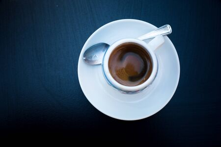One round cup of coffee with white plate and tea spoon on black table. Top view. Morning coffee in bar. Espresso geometrical concept. Coffee-mania, black and white. Isolation with cup of hot beverage 版權商用圖片