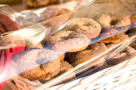 Homemade round biscuits ciambelli with sugar on top packed in white basket with transparent polyethylene film above. Selling sweets in the market. Protective film on food as anti covid measure. Stock Photo