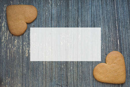 Grey wooden aged background with ginger bread biscuits in two corners wight copy space . Saint valentines frame. Love and wedding invitation wallpaper. Sweetheart picture. Be my Valentine.