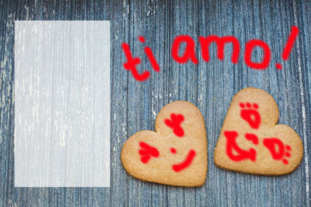 Ginger bread biscuits with fanny faces on grey wooden aged background with semi transparent copy space. Saint valentines frame with love declaration in italian. Ti amo. Invitation wallpaper. Together Stock fotó