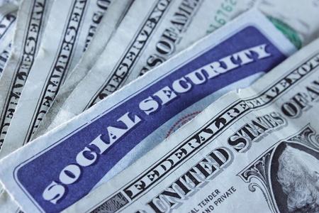 seguro social: Una tarjeta de Seguridad Social rodeada con billetes de d�lar Foto de archivo
