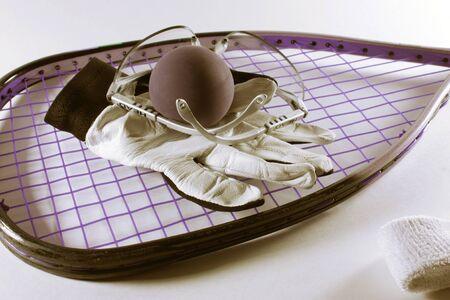 racquetball: Raqueta de Raquetbol, pelota, gafas, guantes y cintillo aislado en un fondo claro