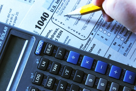 Tax form, calculator and pencil to portray tax time