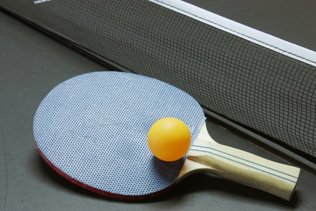 table: Table tennis paddle, ball and table all ready for a game