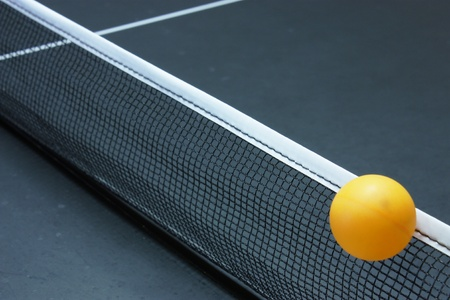 Table tennis ball going over the net Stock Photo