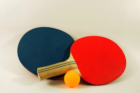 Red and blue table tennis paddles with a yellow ball