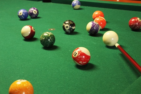 billiards tables: Pool table with balls and stick to play pool Stock Photo
