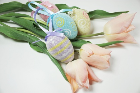 depict: Four easter eggs with three tulips to depict easter