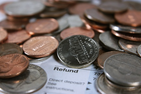 american field service: Coins on a tax form surrounding the word refund. Stock Photo