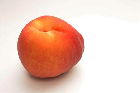 A beautiful fuzzy peach ready to be eaten