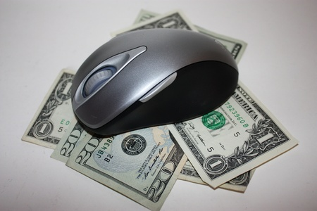 Money with a computer mouse on top to signify online savings photo