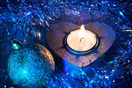 newyears: Blue heart candle and Christmas ball in tinsel Stock Photo
